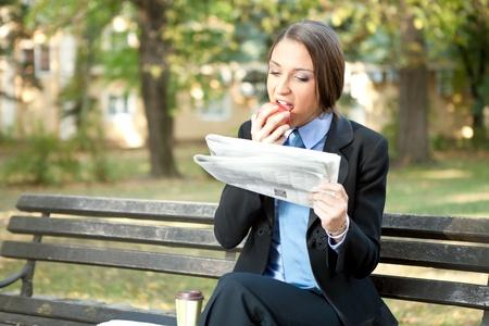banc de parc: d'affaires sur la pomme pause-repas et de lecture de journaux