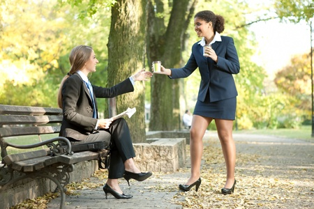 socialize:  young businesswomen together on coffee break in city park