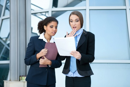 consulted:  businesswomen checking examine paperwork,  Caucasian businesswoman have surprised face  Stock Photo