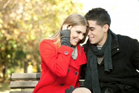 love couple on  sitting on bench, young man whispers to his girlfriend Stock Photo - 11516313