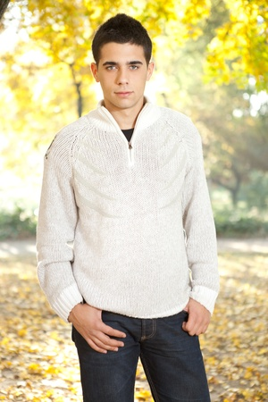 young man in white sweater posing in autumn park