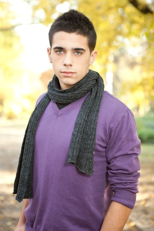 handsome young fashion man posing in autumn park photo