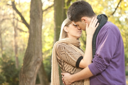 young couple in love kissing in autumn park  photo