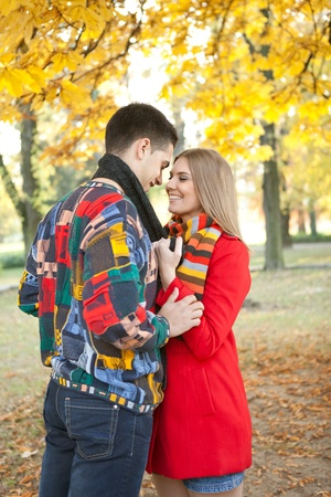 young  romantic  couple kissing under tree in autumn park photo