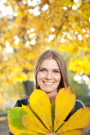 smiling young girl holding big yellow leaf in front  her photo