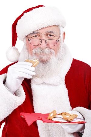 traditionellen Weihnachtsmann essen Lebkuchen, isoliert auf wei�em Hintergrund