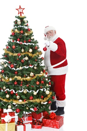 decorating christmas tree: real Santa Claus holding Christmas ball and decorating  Christmas tree, isolated on white background