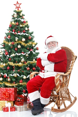 Santa Claus sitting in rocking chair next full decorated Christmas tree, isolated on white background photo