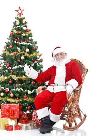 Santa Claus sitting next Christmas tree showing thumb-up sign, isolated on white background photo