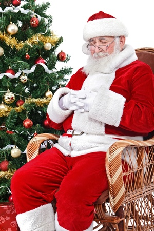 tired Santa Claus sleeping in his rocking chair, isolated on white background photo