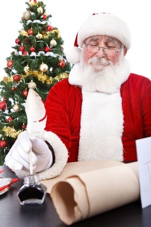 Santa Claus sitting at  desk, writing a list of all the boys and girls who will get Christmas presents , isolated on white background photo