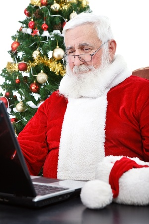 Santa Claus with real beard using laptop, Christmas tree in background photo