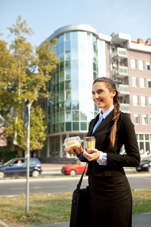 businesswoman  going on work with breakfast in  hands photo