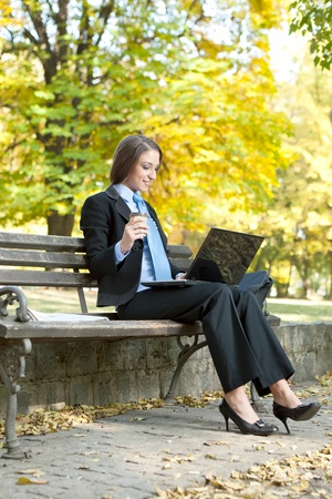 young  businesswoman working on laptop in park photo