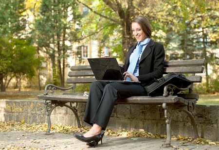 happy young businesswoman  sitting  on bench and looking in laptop photo