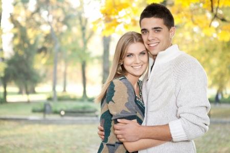 若い男が若いカップル秋の公園で彼のガール フレンドを受け入れる