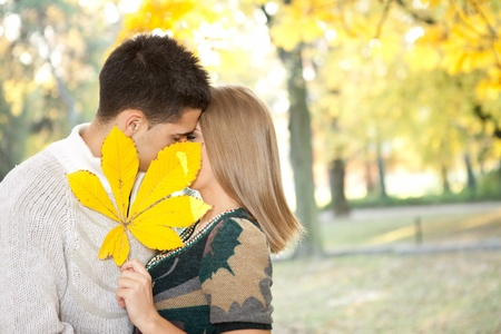young loving couple kissing behind big leaf, hidden kiss  photo