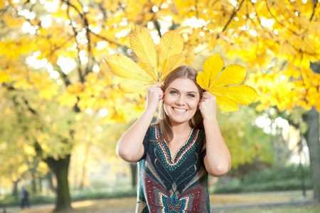 young funny autumn girl holding yellow leaves photo