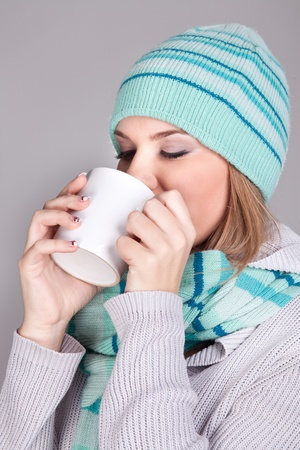 Young woman in winter hat with cup of hot chocolate or coffee or tea Stock Photo - 11735730