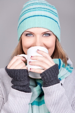 Young beautiful woman wearing winter clothing drinking hot drink photo