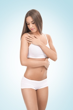 young woman in underwear touching her body,  on blue background photo