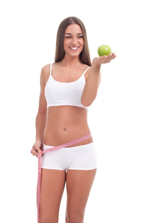 good looking woman on a diet is holding an apple and measuring her waist. photo