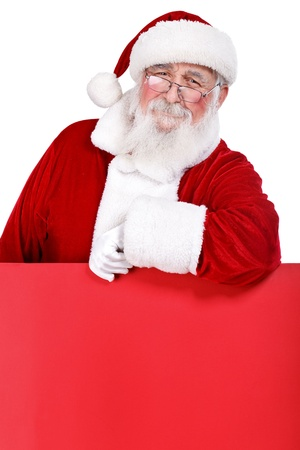 Santa Claus leaning on blank red billboard, isolated on white background photo