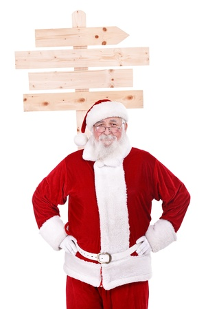 Santa Claus with standing front a wooden sign, isolated on white background photo