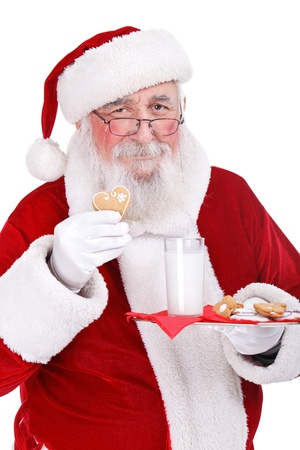 Santa Claus enjoys cookies and milk left out for him, on Christmas eve, isolated on white background photo
