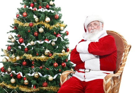 Santa Claus sitting in rocking chair with crossed arms and relax, decorated Christmas tree, isolated on white background photo