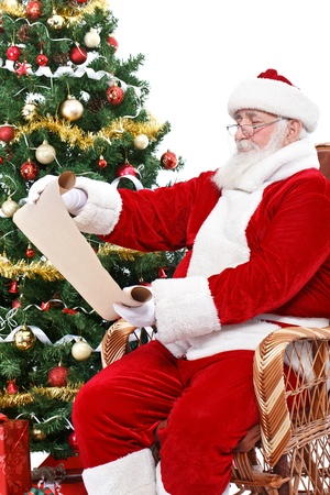 wish list: Santa Claus reading wish list, sitting in rocking chair next  Christmas tree, isolated on white background