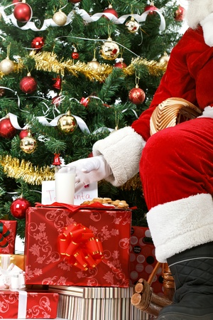 Santa Claus takes a milk and cookie left out for him on Christmas Eve as a thank you gift for leaving presents to a grateful children  photo