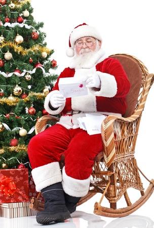 weihnachtsmann: Santa Claus sitzt im Schaukelstuhl und liest Brief mit Kindern w�nschen
