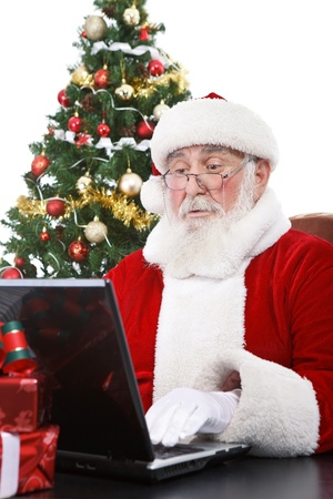 real Santa Claus working on laptop with surprised face, isolated on white background photo