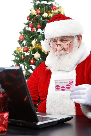 Santa Claus buying on-line using credit card, isolated on white background  photo