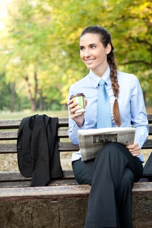 sitting on a bench: smiling businesswoman in park on cafe break