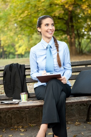 overworked businesswoman, smiling woman working in park  Stock Photo - 11859777
