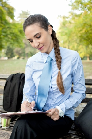 businesswoman making note in park,  overworked photo
