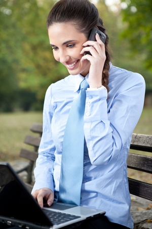 busy businesswoman working in park with laptop and phone photo