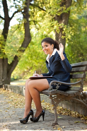 afro, smiling  young businesswoman waving hello, sitting  in park Stock Photo - 11860048