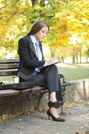 young businesswoman writing , making note on break , outdoor photo