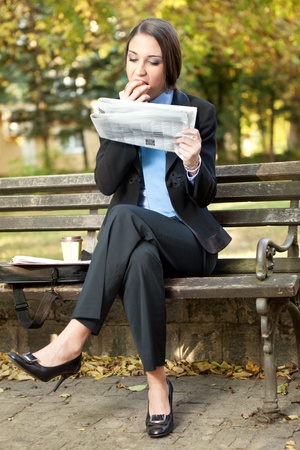 young businesswoman in park on break eating and reading newspaper photo