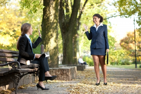 two young,  smiling business women meet in park photo