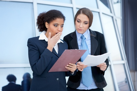 consulted:  two businesswomen checking document , terrible mistake