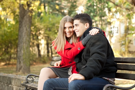 young affectionate couple hugging on bench in park  photo