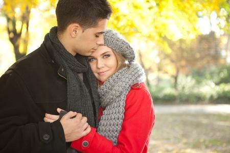 가을 공원에서 껴안은 로맨틱 젊은 부부