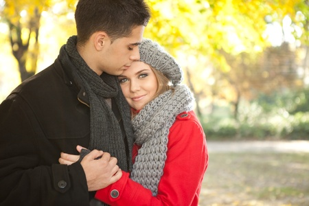 romantic young couple embracing in autumn park Фото со стока