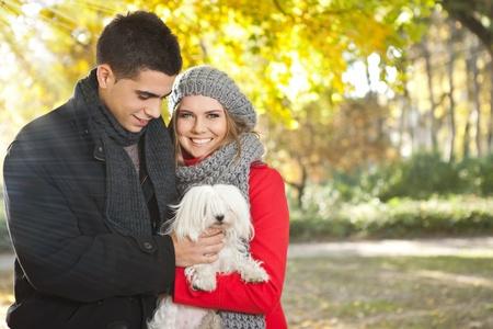 A pie de otoño, joven pareja feliz con el perro Foto de archivo