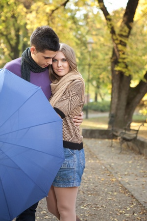 young romantic couple in autumn park embracing photo