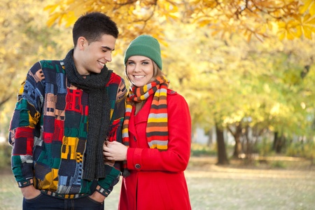 young love couple felling cold in autumn park photo